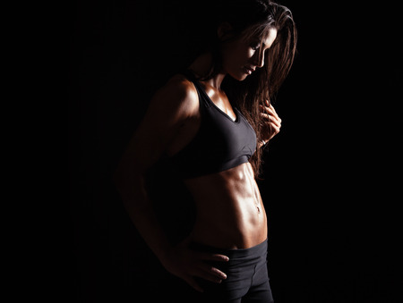Foto de Image of female in sports clothing relaxing after workout on black background. Muscular female body with sweat. - Imagen libre de derechos