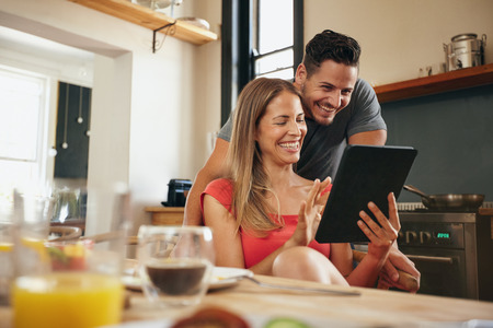 Photo pour Happy young couple in the modern kitchen in the morning, using a digital tablet. Smiling young woman showing something to her boyfriend in touchpad. - image libre de droit