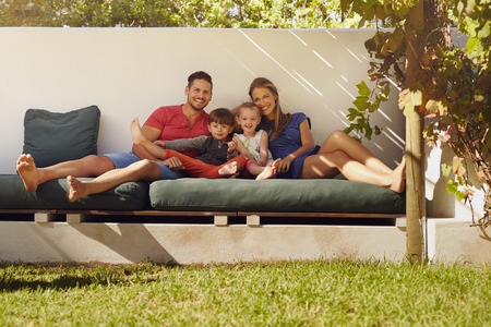 Portrait of happy young family sitting on patio smiling at camera. Couple with kids sitting on couch in their backyard.
