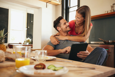 Photo pour Shot of loving young couple in kitchen by breakfast table in morning. Man using digital table while woman hugging him from behind, both looking at each other smiling. - image libre de droit