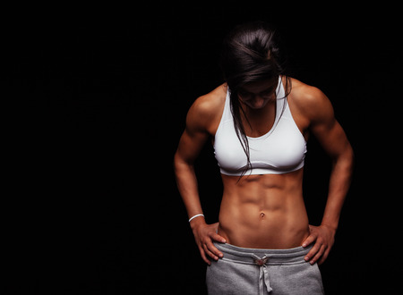 Foto de Image of young woman in sports clothing looking down against black background with copyspace. Muscular build female after workout. - Imagen libre de derechos