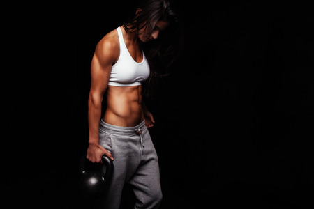 Photo for Young fit woman holding kettle bell exercising against black background. Muscular female doing crossfit exercise. - Royalty Free Image