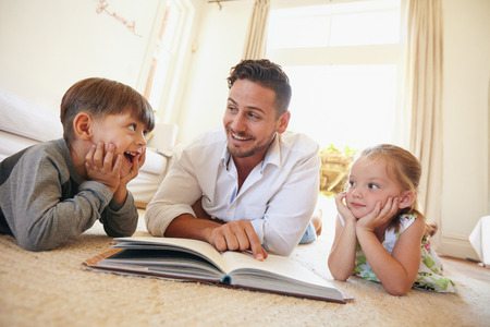 Photo pour Shot of happy young family lying on the floor reading a book. Young man reading stories to his little son and daughter at home. - image libre de droit