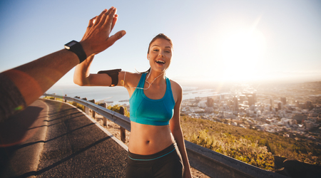 Foto de Fit young woman high fiving her boyfriend after a run. POV shot of runners on country road looking happy outdoors with bright sunlight. - Imagen libre de derechos
