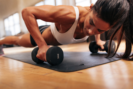 Photo pour Strong young woman doing push ups exercise with dumbbells. Fitness model doing intense training in the gym. - image libre de droit