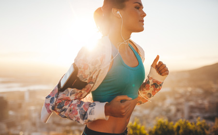 Photo pour Close-up shot of fitness woman running outdoors. Caucasian female jogging in morning with bright sunlight. - image libre de droit