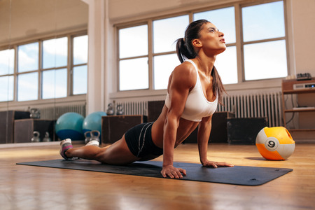 Foto de Woman doing core stretch on fitness mat. Muscular young woman doing stretching exercise in gym. - Imagen libre de derechos