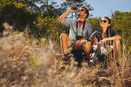 Foto de Outdoor shot of young couple sitting together taking a break on hike. Caucasian man and woman drinking water while out hiking. - Imagen libre de derechos