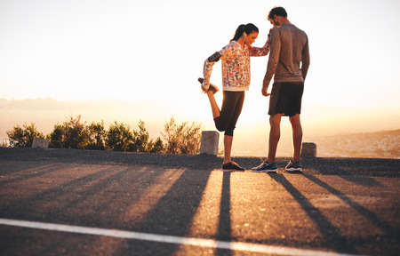 Foto de Outdoor shot of fit young joggers stretching before a run together in morning. Young man standing and woman stretching her legs at sunrise. - Imagen libre de derechos
