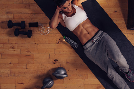 Foto de Sporty young woman lying on exercise mat doing sit-ups. Top view of muscular woman doing abs crunches in gym. - Imagen libre de derechos