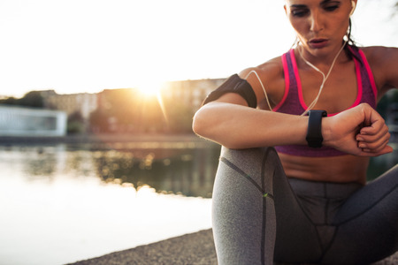 Photo pour Beautiful young woman sitting outdoors using a smartwatch to monitor her progress. Caucasian female runner resting and checking her performance on fitness smart watch device. - image libre de droit