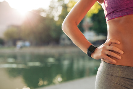 Foto de Sportswoman wearing smartwatch device. Cropped shot of fit woman in sports wear standing with her hand on hip outdoors, with sun flare. - Imagen libre de derechos