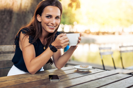 Photo for Portrait of beautiful young woman sitting at a table with a cup of coffee in hand looking at camera smiling while at cafe. - Royalty Free Image