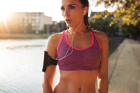 Photo for Young woman runner wearing armband and listening to music on earphones. Fit sportswoman taking a break from outdoors training. - Royalty Free Image