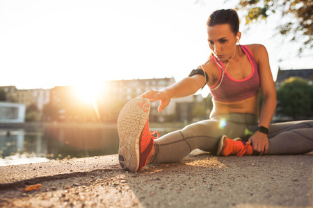 Foto de Fitness woman stretching before a run. Young female runner stretching her muscles before a training session. She is sitting on sidewalk along a pond in city on a sunny day with sun flare. - Imagen libre de derechos