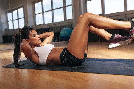 Foto de Young woman doing pilates, working on abdominal muscles. Fitness woman exercising to  improve core muscle strength in gym. - Imagen libre de derechos