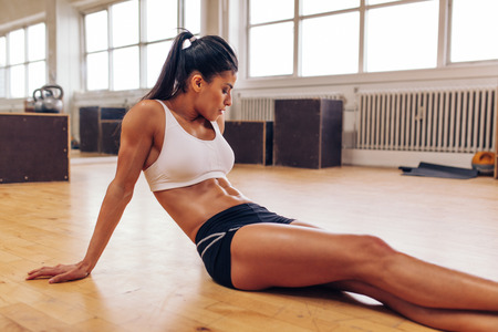 Photo pour Portrait of muscular young woman relaxing after workout at gym. Fit female athlete taking a break from workout. - image libre de droit