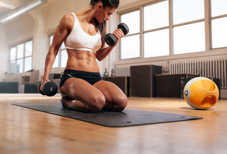 Photo for Physically fit woman at the gym lifting dumbbells to strengthen her arms and biceps. Muscular woman sitting on exercise mat looking at her arms. - Royalty Free Image