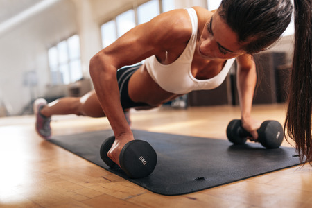 Foto de Gym woman doing push-up exercise with dumbbell. Strong female doing crossfit workout. - Imagen libre de derechos