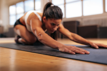 Foto de Woman doing stretching workout on fitness mat, focus on hands, fitness female performing yoga on exercise mat at gym. - Imagen libre de derechos