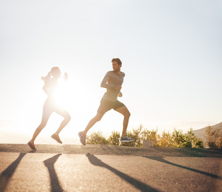 Photo pour Young people running on country road with bright sunlight. Outdoor shot of young man and woman jogging in morning. - image libre de droit