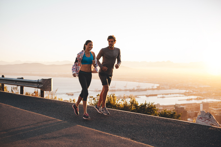 Photo pour Young couple jogging early in morning. Young man and woman running outdoors on a hillside road. - image libre de droit