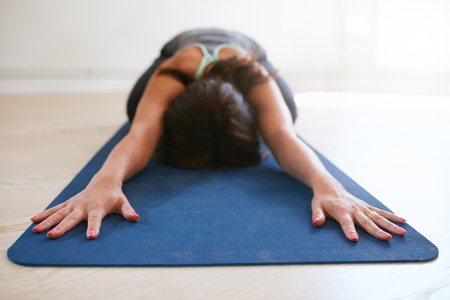 Foto de Woman doing stretching exercise on yoga mat. Fitness female performing yoga on exercise mat at gym. Child Pose, Balasana. - Imagen libre de derechos