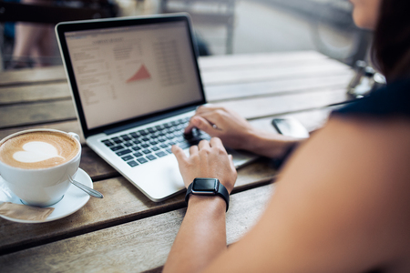 Photo for Cropped shot of a woman at cafe working on her laptop computer. Female wearing smartwatch using laptop with a coffee cup on table. - Royalty Free Image