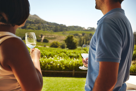 Photo pour Couple standing together holding glasses of white wine with vineyard in background. Man and woman standing outdoors drinking wine at winery. - image libre de droit