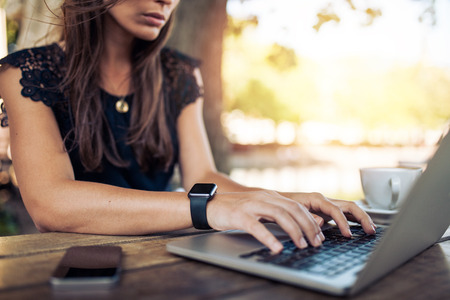 Photo pour Young woman wearing smartwatch using laptop computer. Female working on laptop in an outdoor cafe. - image libre de droit