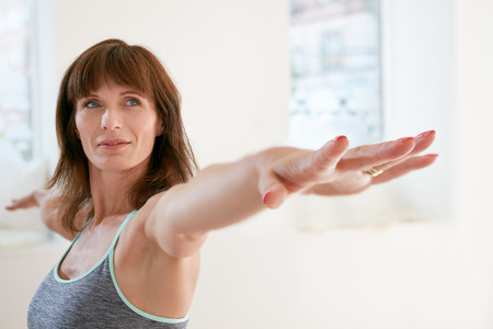 Foto de Portrait of fitness woman stretching her hands and looking away. Attractive mature woman exercising yoga in Virabhadrasana  pose. Female doing warrior pose in gym. - Imagen libre de derechos