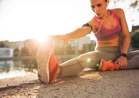 Photo for Young woman runner stretching legs before doing her summer workout. Sportswoman warming up before outdoor workout. - Royalty Free Image
