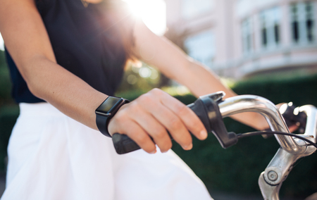 Photo pour Woman riding a bike with a smartwatch. Female wearing smart watch while cycling. Smart watch concept. - image libre de droit