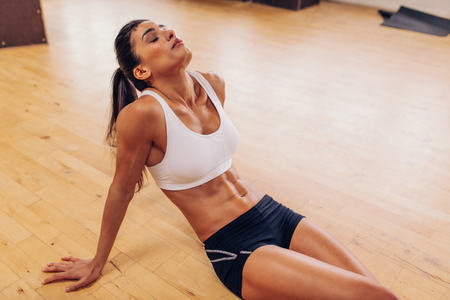 Foto de Portrait of tired woman having rest after workout. Tired and exhausted female athlete sitting on floor at gym. - Imagen libre de derechos