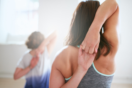 Photo pour Rear view of fit woman doing gomukhasana in yoga class. Fitness female holding hands behind their back and stretching. Triceps and shoulders workout. - image libre de droit