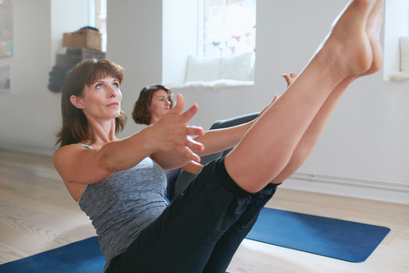 Photo pour Women practicing stretching and yoga workout exercise together in a health club gym training class session. Two women practicing yoga, bending in boat pose. Performing Navasana in yoga class. - image libre de droit
