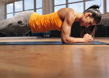 Foto de Young woman doing pilates, working on abdominal muscles. Muscular female doing core workout in the gym. - Imagen libre de derechos
