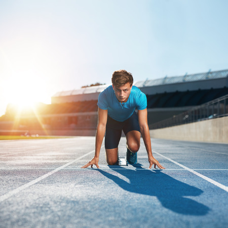 Photo pour Fit and confident man in starting position ready for running. Male athlete about to start a sprint looking at camera with bright sunlight. - image libre de droit