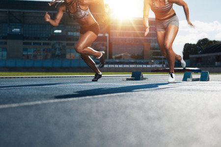 Photo pour Sprinters starts out of the blocks on athletics racetrack with bright sunlight. Low section shot of female athletes starting a race in stadium with sunflare. - image libre de droit