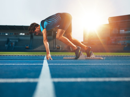 Photo pour Male athlete on starting position at athletics running track. Runner practicing his sprint start in athletics stadium racetrack. - image libre de droit