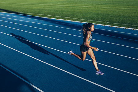 Photo pour Outdoor shot of young African woman athlete running on racetrack. Professional sportswoman during running training session. - image libre de droit