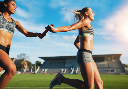 Photo for Female athletes passing over the baton while running on the track. Young women run relay race, track and field event. - Royalty Free Image