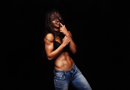 Foto de Portrait of happy young woman standing against black background. Female model posing in bra and jeans. Funny woman biting her finger. - Imagen libre de derechos
