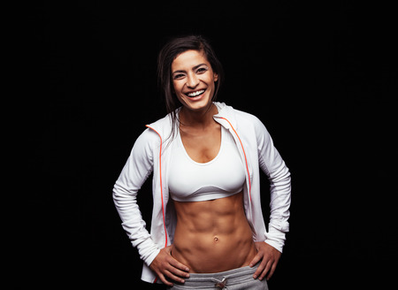 Foto de Happy young woman in sports clothing standing with hands on hips smiling. Muscular fitness model on black background. - Imagen libre de derechos