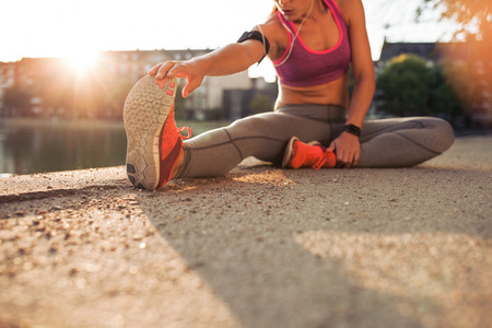 Photo for Cropped shot of female runner stretching legs before doing her summer workout. Woman warming up before outdoor workout with sun flare. - Royalty Free Image
