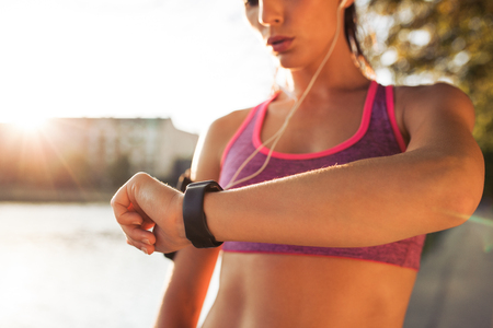 Foto per Young fitness woman looking at her smart watch while taking a break from outdoor workout. Sportwoman checking pulse on fitness smart watch device. - Immagine Royalty Free