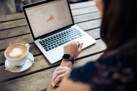 Photo for Female hand wearing a smartwatch sitting at a table with laptop and cup of coffee. Woman working on laptop at cafe. - Royalty Free Image