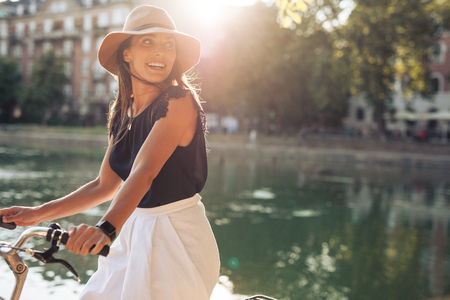 Photo pour Portrait of happy young woman riding bicycle by a pond. Woman wearing a hat on a summer day looking over her shoulder. - image libre de droit