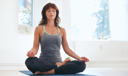 Photo for Woman sitting on exercise mat in lotus position with her eyes closed doing yoga. Fit caucasian female practicing Padmasana at gym. - Royalty Free Image