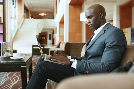 Foto de Image of busy young businessman working on laptop. African businessman sitting in hotel lobby waiting for someone. - Imagen libre de derechos